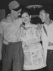 Lee Hoffman wears a dress made of the pages of her zine Quandry to Worldcon, 1952. With Walt Willis (left) and Max Keasler (right)